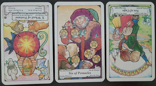 Three cards from the Hanson Roberts deck are laid out on a black table. In order from left to right, they are as follows: The Wheel of Fortune Reversed, the Six of Pentacles, and the Ten of Cups Reversed.